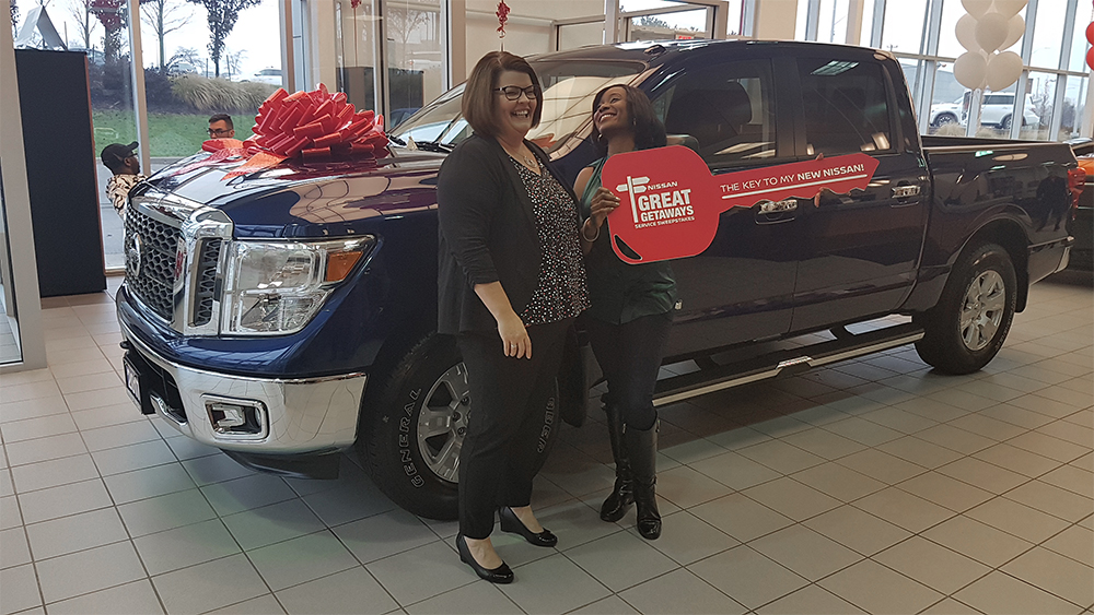 Cherie presenting Eniola with her key to her new 2017 Nissan Titan