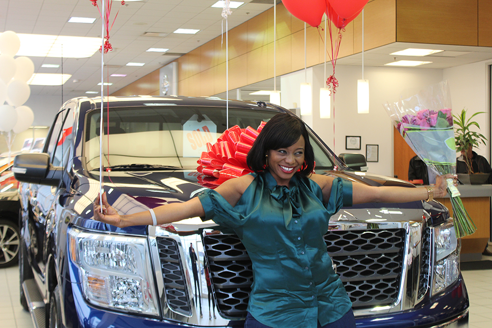 Eniola posing in front of her new 2017 Nissan titan she won as part of the Nissan Great Getaways Service Sweepstakes